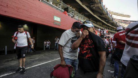 Aficionados se tapan tras los incidentes en el Monumental. (AFP)