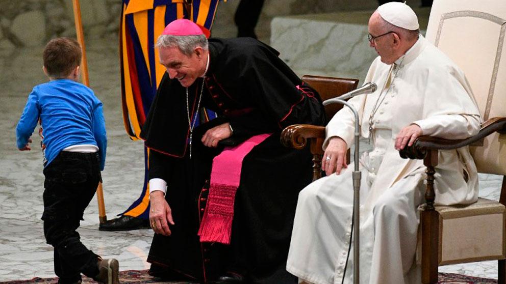 El Papa Francisco y el el Prefecto de la Casa Pontificia sonríen ante la interrupción de un niño con síndrome de Down. Foto: AFP