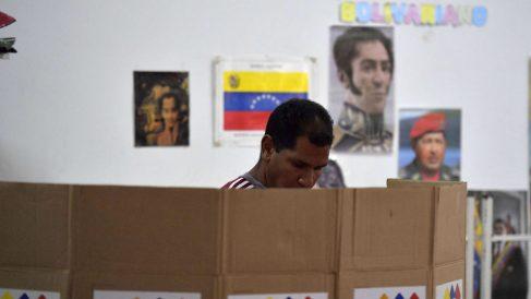 Un hombre deposita su voto en Venezuela