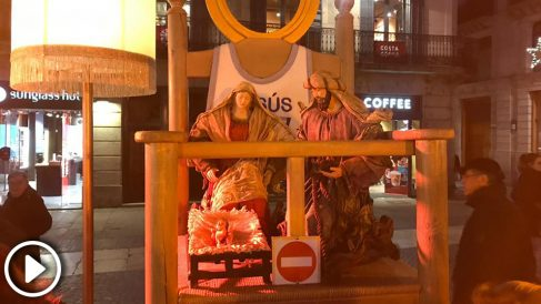 Un grupo de jóvenes colocan un pesebre de verdad en una de las sillas vacías del belén navideño de Ada Colau