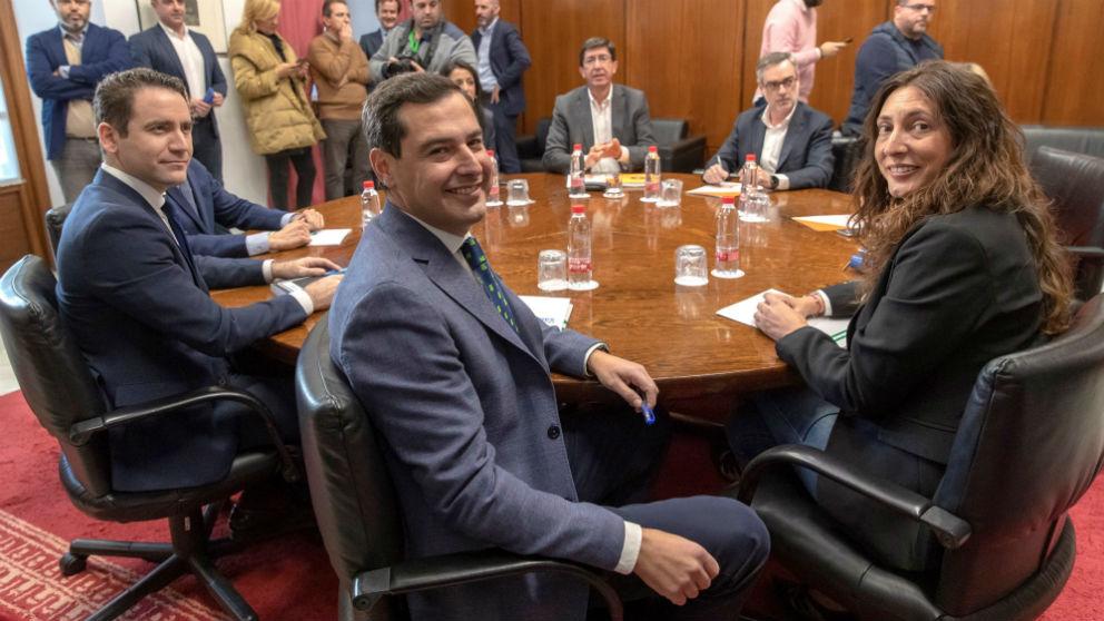Los equipos negociadores de Partido Popular y Ciudadanos, encabezados por Juanma Moreno (c) y Juan Marín (al fondo) al comienzo de la segunda reunión en el Parlamento andaluz en Sevilla para tratar sobre el cambio de Gobierno en Andalucía.