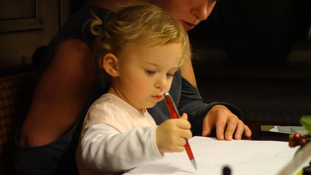 Una niña con su madre dibujando.