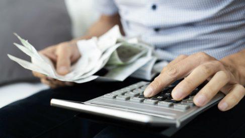 Hombre joven con facturas y calculadora (Foto: iStock)