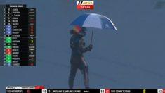Fernando Alonso, tras salir del Cadillac paraguas en mano.