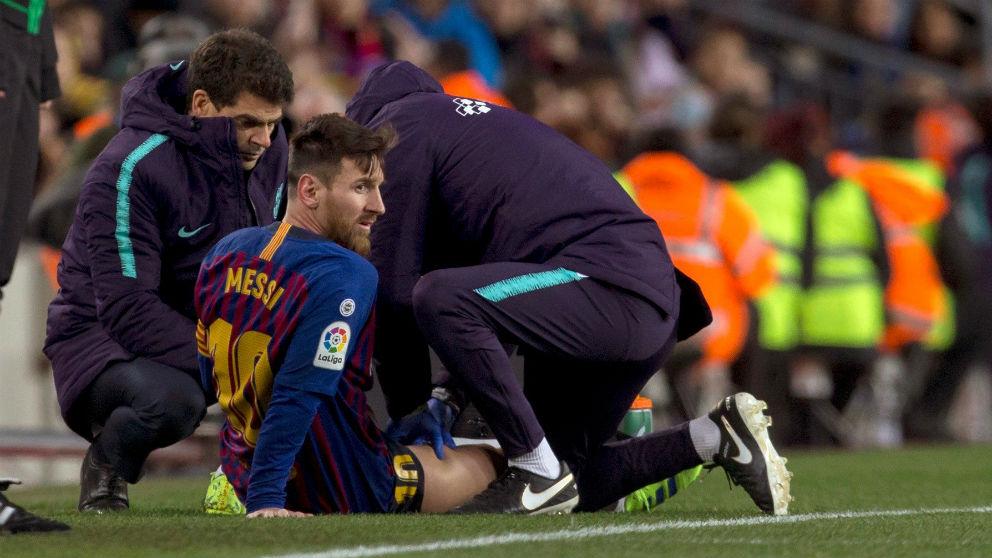 Messi es atendido en la banda del Camp Nou. (EFE)