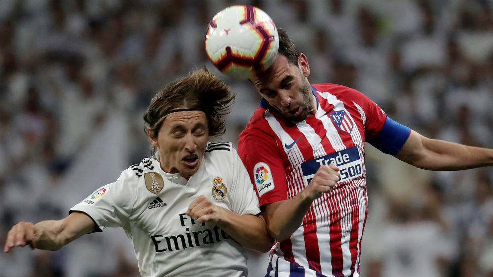 Modric y Godín disputan un balón en el derbi. (Getty)