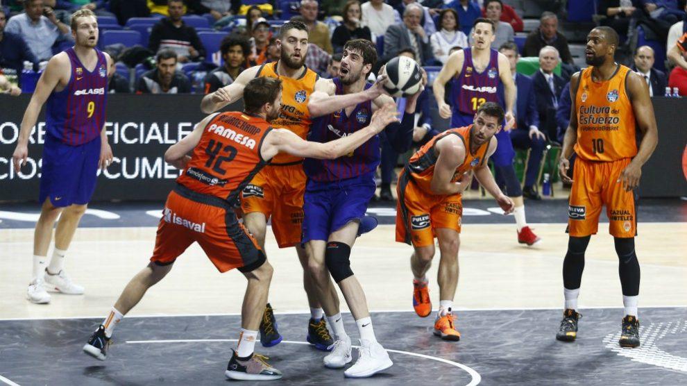 Tomic pelea por un balón con los interiores del Valencia. (ACB)
