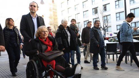 Manuela Carmena en silla de ruedas empujada por José Manuel Calvo. (Foto. Madrid)