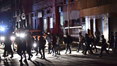 Ciudadanos de Venezuela caminan por las calles oscuras de Venezuela tras el apagón del suministro eléctrico. Foto: AFP