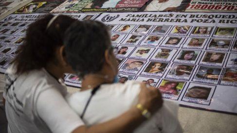 Madre e hija buscan en un mural las fotos de sus familiares desaparecidos en México. Foto: AFP