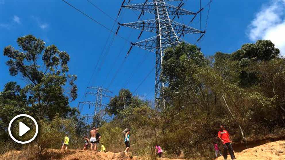 Venezolanos en un poste eléctrico. Foto: AFP