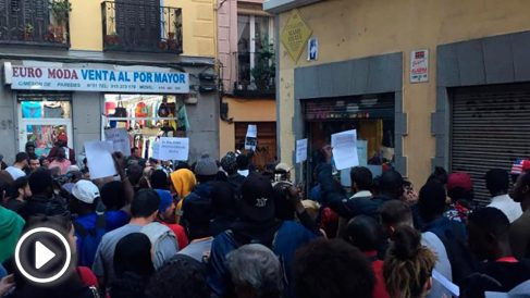 Un grupo de personas se concentra en torno a la pancarta que Carmena ha colocado en Lavapiés en memoria del 'mantero' muerto. Foto: Europa Press