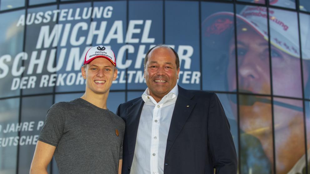 Mick Schumacher posa con el multimillonario Andreas Pohl delante de la exposición en homenaje a su padre.
