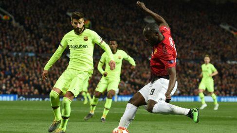 Gerard Piqué intenta robarle un balón a Romelu Lukaku durante el Manchester United – Barcelona. (AFP)