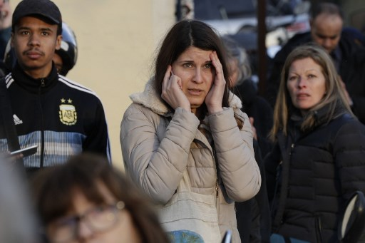 Una mujer habla por teléfono consternada ante la catedral Notre Dame de París en llamas. Foto: AFP