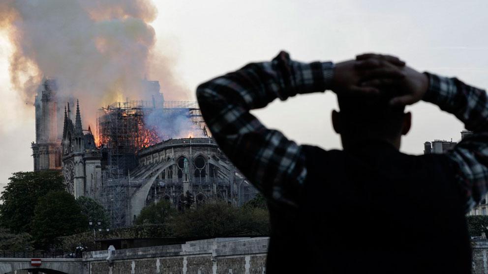 Un hombre se lleva las manos a la cabeza viendo el incendio de la catedral Notre Dame de París. Foto: AFP