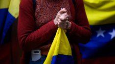 Una mujer sostiene entre sus manos una bandera de España. Foto: AFP