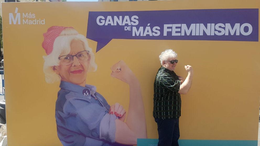 Almodóvar frente a un cartel de Más Madrid