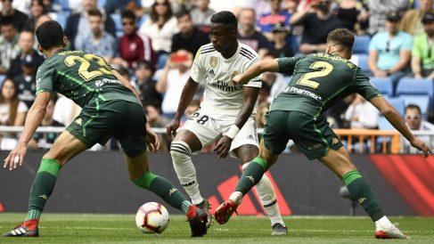 Vinicius encara a dos jugadores del Betis en el último partido de Liga en el Bernabéu. (AFP)