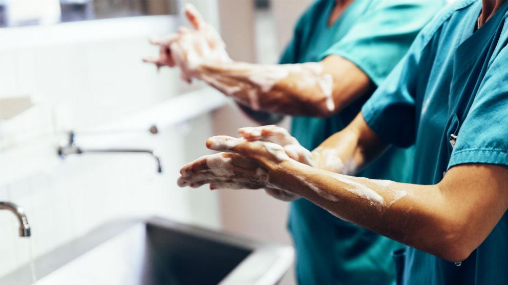 Pareja de cirujanos se lavan las manos antes de entrar a operar (Foto: iStock)