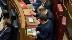 Jordi Turull y Jordi Sánchez usan sus teléfonos móviles aprovechando su 'escapada' de la cárcel al Congreso de los Diputados. Foto: Twitter