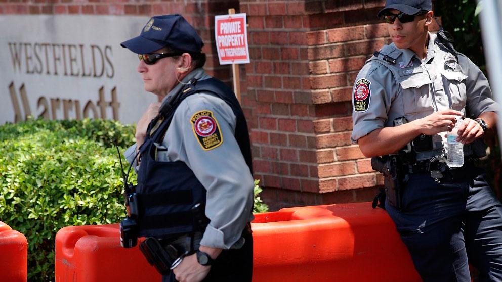 Dos agentes custodian la entrada al lugar donde se celebró la reunión anual del club Bilderberg en 2018. Foto: AFP