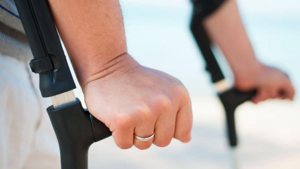 Una enferma de esclerosis múltiple camina ayudada de unas muletas.