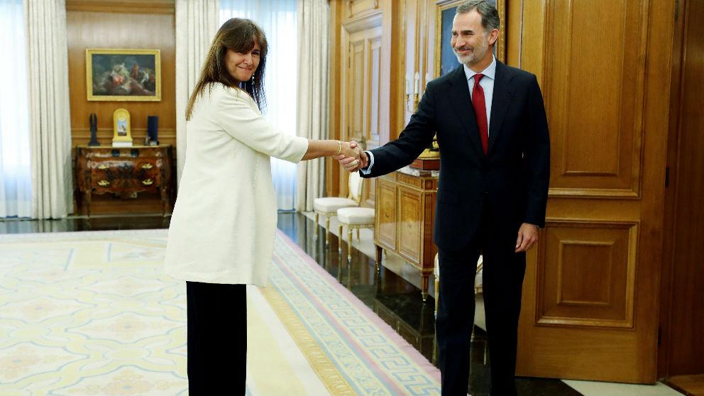 Laura Borrás, de JxCAT, muestra su pulsera amarilla mientras estrecha la mano del Rey, esta mañana, en le Palacio de la Zarzuela. (EFE)