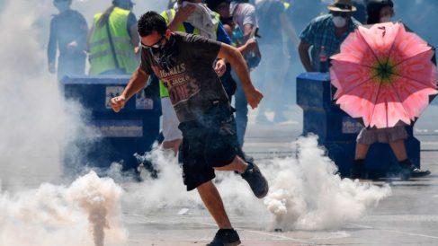 Un manifestante de los llamados «chalecos amarillos» devuelve a la Policía una bomba de gas lanzada para reprimir las violentas protestas. Foto: AFP