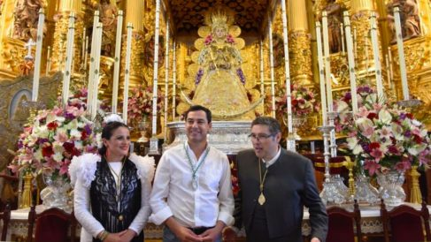 El presidente de la Junta de Andalucía, Juanma Moreno (c), delante de la Virgen del Rocío. (Foto: @JuanMa_Moreno)