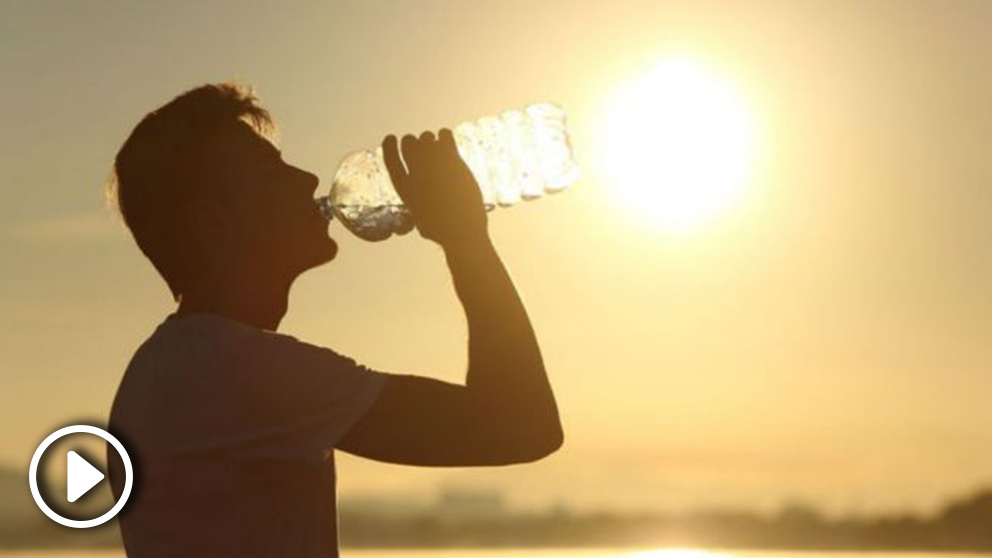 Un joven se hidrata bajo el sol