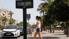 Una mujer camina junto a un termómetro que marca 43 grados en las calles de Córdoba (Foto: EFE).