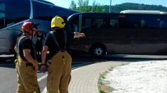 Dos bomberos junto a la zona de la provincia de Lérida donde han chocado los dos autobuses provocando cortes de tráfico.