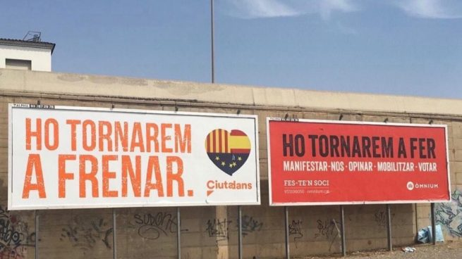 Una valla publicitaria de Ciudadanos, junto a la de Òmnium.