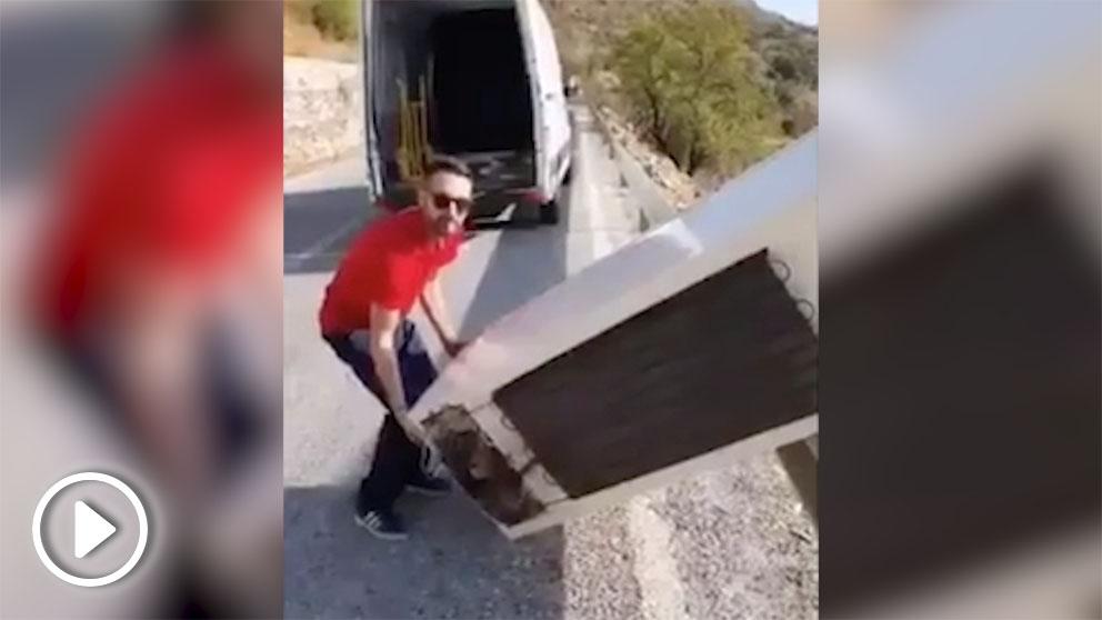 Momento en que el trabajador de la empresa de residuos arroja el frigorífico por el barranco.