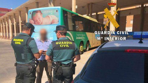 Agentes de la Guardia Civil junto al autobús en el que escapó la víctima.