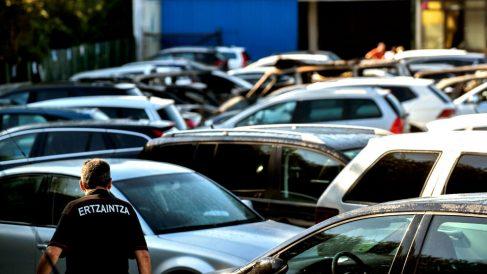 Un agente de la Ertzaintza inspecciona el parking afectado por el incendio (Foto: EFE).