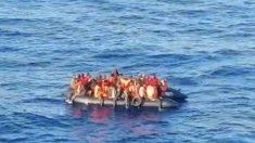 Una patera con inmigrantes a bordo fotografiada desde un barco.