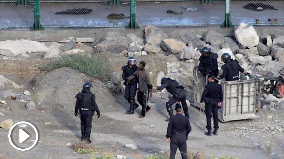 Agentes del GRS de la Guardia Civil detienen a algunos de los inmigrantes que asaltaron la valla de Ceuta.