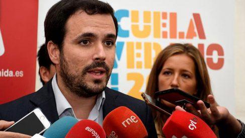 El coordinador general de IU y diputado de Unidas Podemos, Alberto Garzón (c), atiende a los medios de comunicación este viernes, antes de inaugurar la Escuela de Verano de IU, celebrada en La Granja, Segovia. Foto: EFE