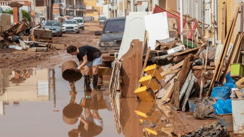 Una mujer afectada por la Gota Fría trata de reparar los destrozos en su vivienda.