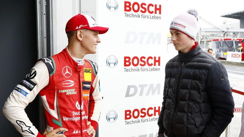 Mick Schumacher habla con su primo David en una carrera.