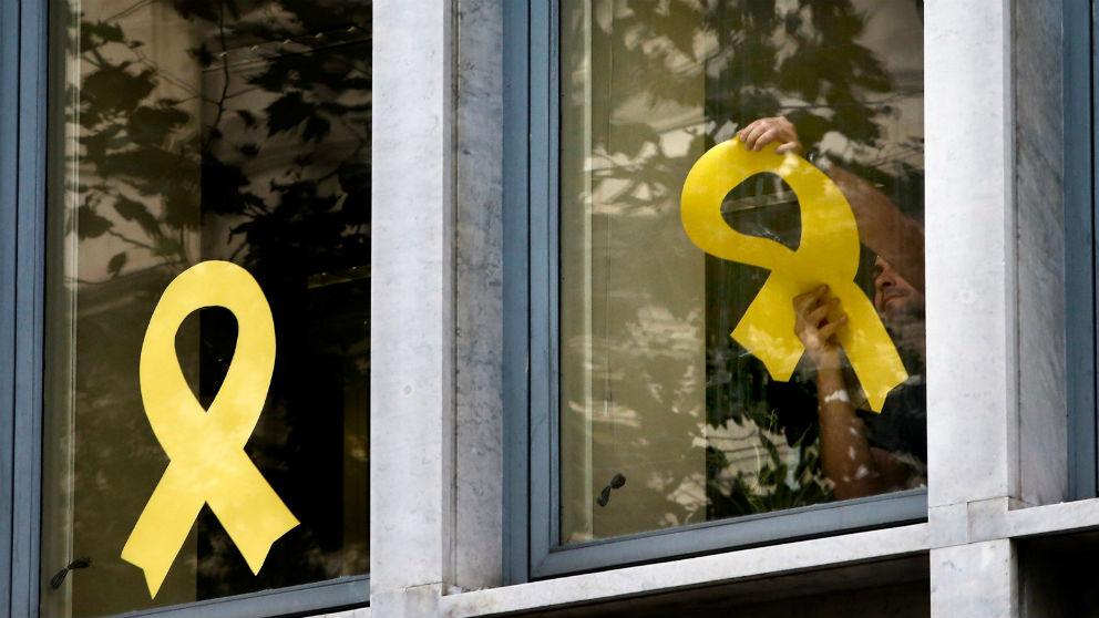 Trabajadores del Departamento de Agricultura Ganadería, Pesca y Alimentación de la Generalitat retiran los lazos amarillos de las ventanas (Foto: EFE).