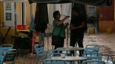DOs personas se refugian de la lluvia bajo la sombrilla de un bar. Foto: EP