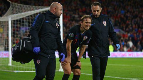 Modric se retira dolorido del terreno de juego. (AFP)