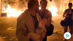 Un padre con su bebé en brazos huye de las llamas.