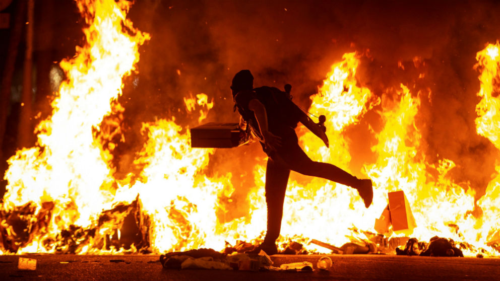 Un CDR avivando una hoguera junto a la Delegación del Gobierno en Barcelona. (Foto: EFE)