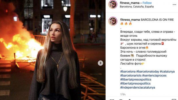 La instagramer rusa @fitness_mama con una barricada ardiendo de Barcelona detrás.