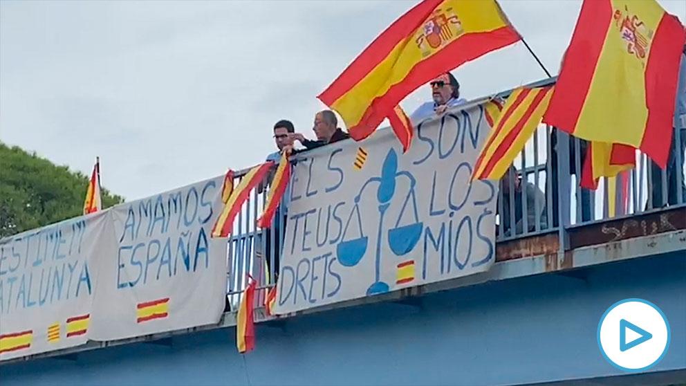 Banderas de España sobre un puente en una de las carreteras cortadas a causa de la huelga general en Cataluña.