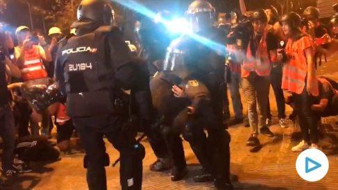 El policía herido en la plaza Urquinaona mientras es llevado inconsciente por compañeros.